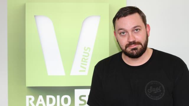 Technoproduzent Fritz Kalkbrenner vor grünem Virus-Logo