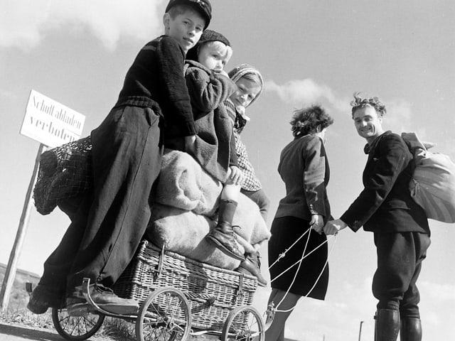 Drei Kinder und Proviant auf einem Leiterwagen, gezogen von den Eltern.