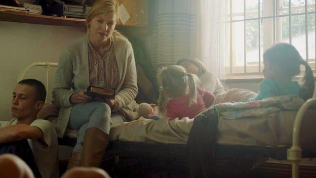 Eine Mutter mit vier kleinen Kindern auf dem Bett.