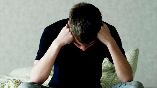 Ein junger Mann sitzt mit aufgestütztem Kopf auf einem Bett.