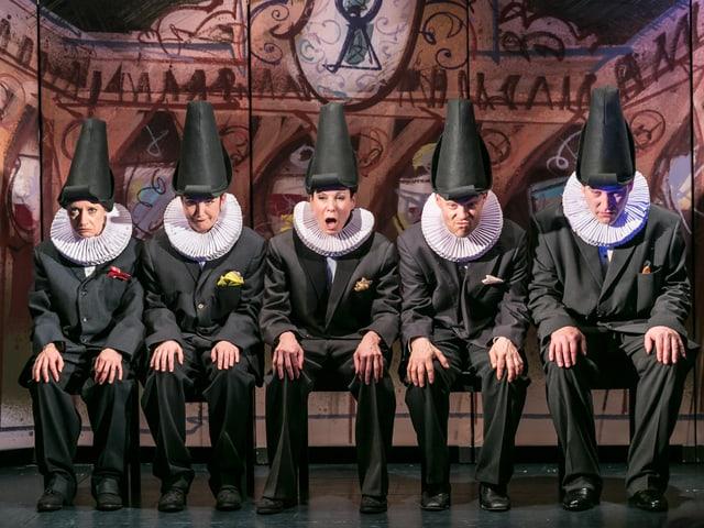 Fünf Figuren mit Rüschenkragen und spitzem Hut