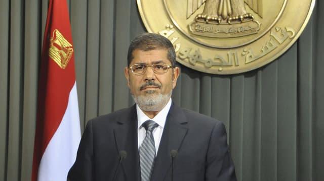Präsident Mursi hält eine Rede – im Hintergrund die ägyptische Flagge.