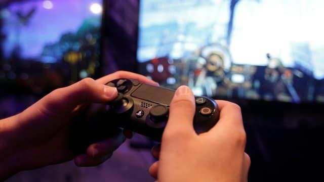 Zwei Hände halten einen Playstation-4-Controller.