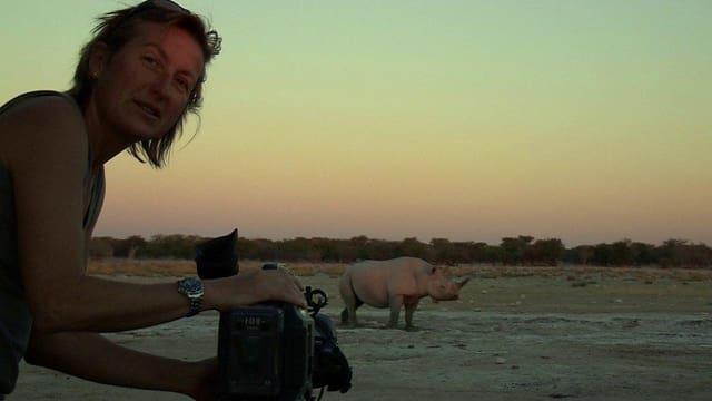 Die Kamerafrau Justine Evans filmt in der Dämmerung ein Nashorn.