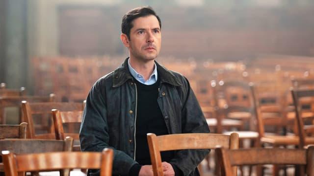 Ein Mann mit ernstem Gesicht sitz alleine in einem Raum voller leerer Stühle.