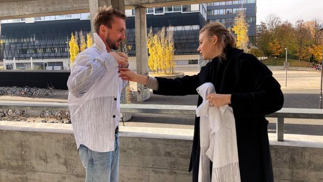 ein junger Mann probiert ein Hemd-Muster an, eine junge Frau testet das Material