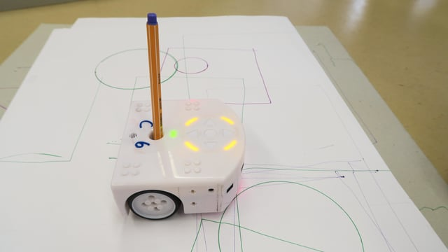 Ein weisses Kästchen mit einem Filzstift malt Linien auf ein Papier.