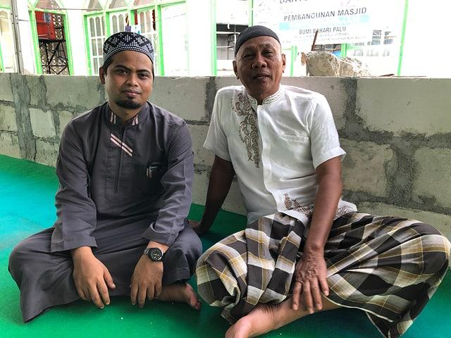 Imam und weiterer Mann sitzen im Schneidersitz auf dem Boden der zerstörten Moschee.