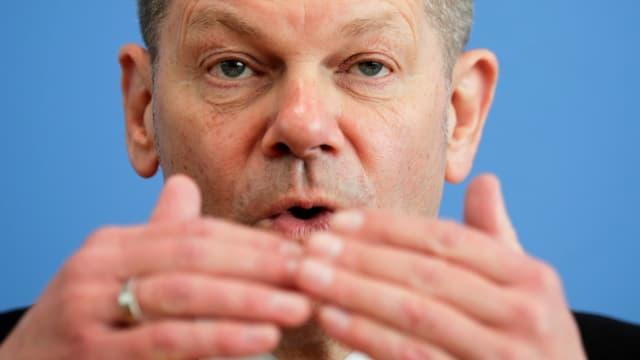 Olaf Scholz mit vorgehaltenen Händen im Porträt.