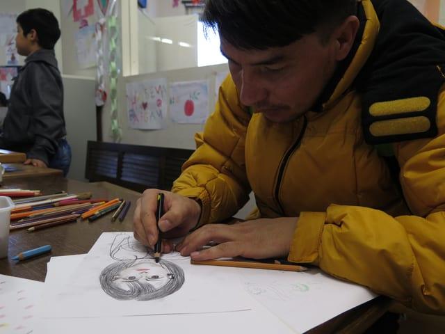 Mann zeichnet das Bild einer Frau.