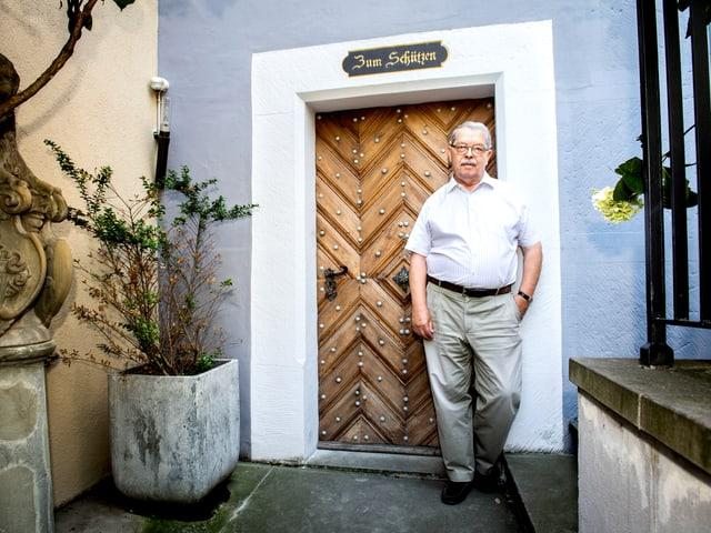 """Ein älterer Herr steht vor seiner Haustür. Über der Tür steht """"Zum Schützen"""" angeschrieben."""