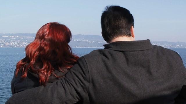 Ein Paar sitzt auf einer Bank und blickt über den Zürichsee