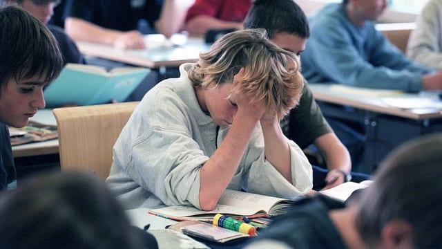 Ein Bub im Klassenzimmer. Er stützt seinen Kopf in seinen Händen.