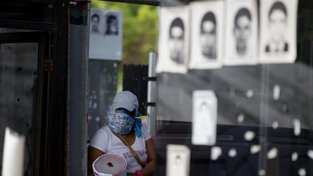 Verhüllte Frau vor Postern der Vermissten.