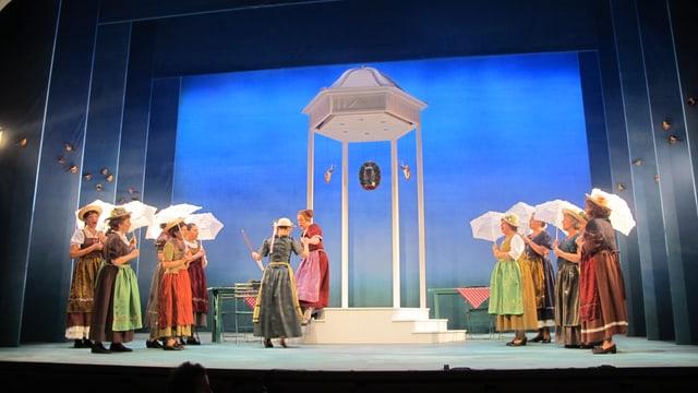 Blick auf die blau getönte Bühne, Frauen mit Kostümen.