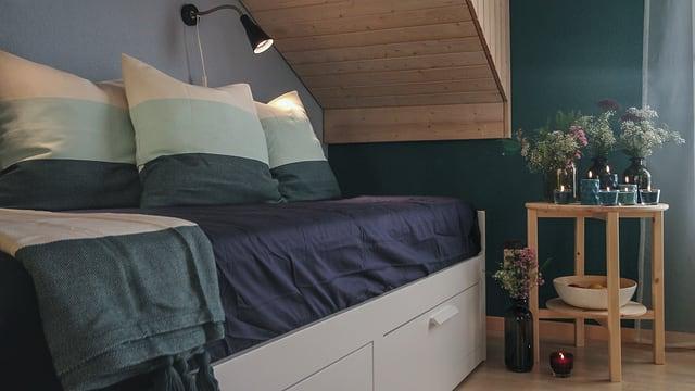 In der Erholungsecke stehen ein Bettsofa und einen hölzernen Beistelltisch. Die türkis-blauen Farben bringen Ruhe in den Raum.