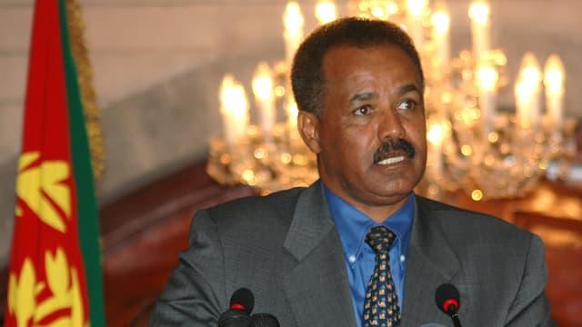 Der eritreische Staatspräsident Isayas Afewerki sitzt hinter Mikrofonen neben einer Fahne.