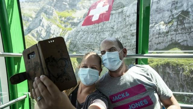 Zwei Gäste mit Gesichtsmaske in der Seilbahnkabine am Säntis