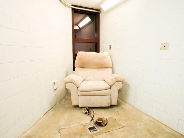 Ein Sofa steht in einem engen, weissen Raum.