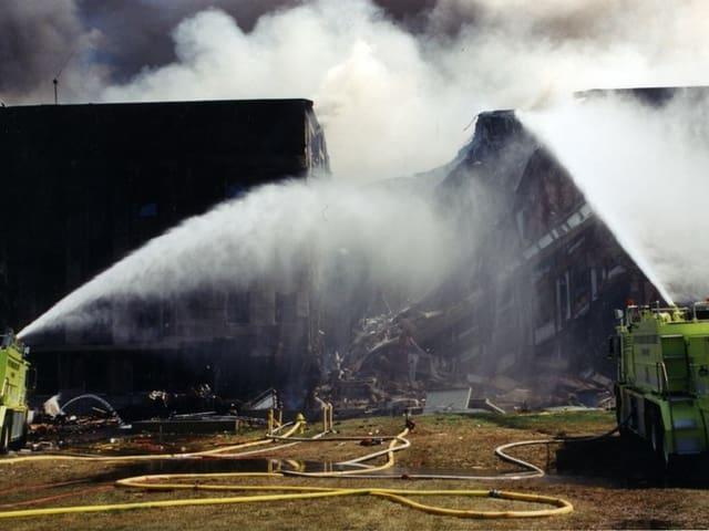 Rauchende Gebäudeteile werden mit Löschwasser bespritzt.