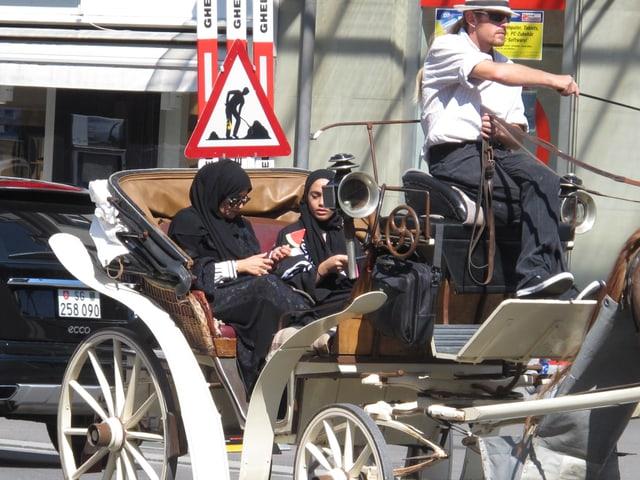 Zwei arabische Touristinnen in einer Kutsche in Interlaken.