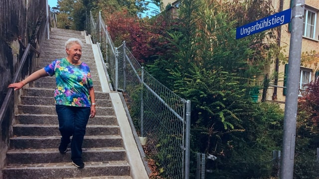 Eine ältere Dame steigt eine Treppe runter.