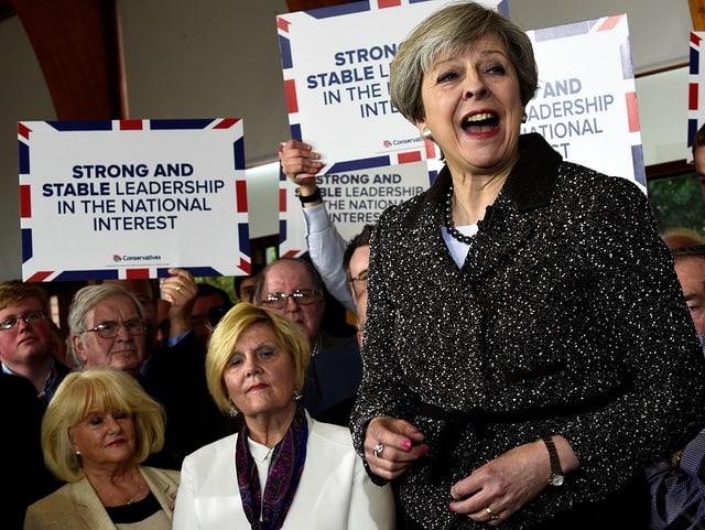 May erhöht und von Anhängern umringt, die Transparente mit ihrem Wahlkampfmotto hoch halten.