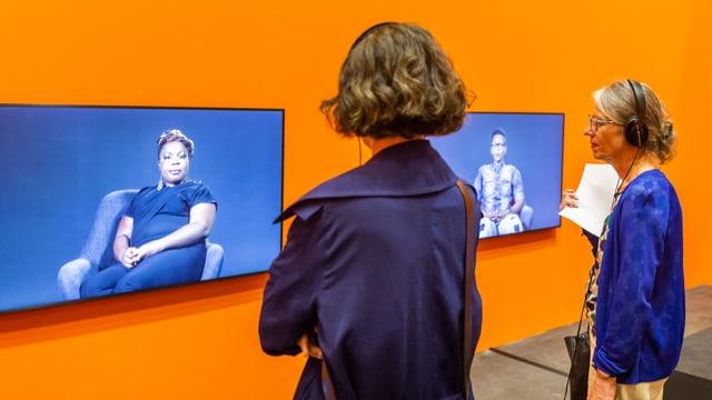 Zwei Frauen stehen vor zwei Bildschirmen