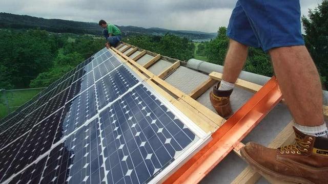 Zwei Männer bedecken ein Dach mit Solarpanels.