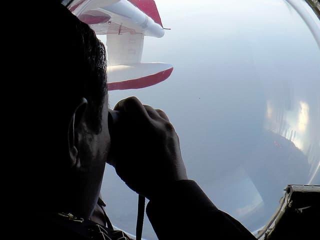 Ein Mann mit Fernglas schaut durch ein Flugzeugfenster.