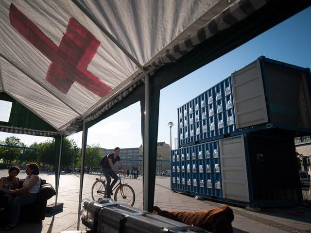 Blick aus einem weissen Zelt mit rotem Kreuz auf die blauen Schiffscontainer.