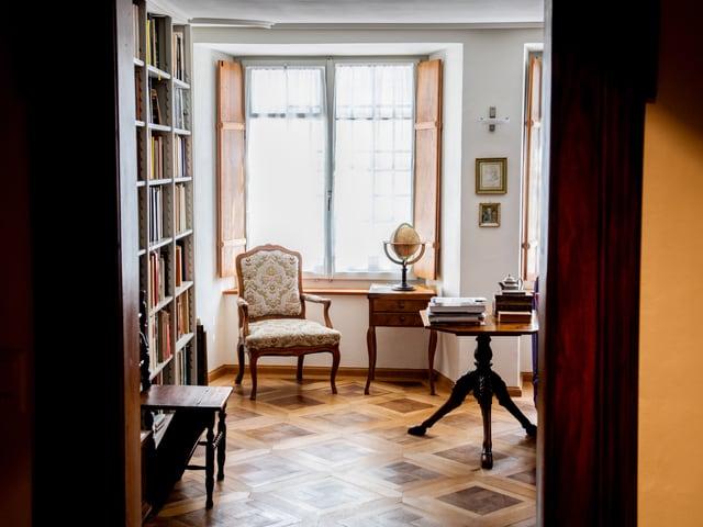 Ein Blick in ein Wohnzimmer mit Parkettboden, Bücherregal, Sessel.