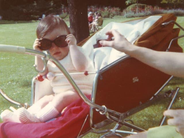 Ein Kleinkind sitzt mit einer übergrossen Sonnenbrille in einem Kinderwagen.