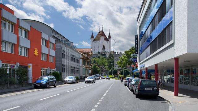 Strasse mit Thuner Schloss und Parkplätzen.