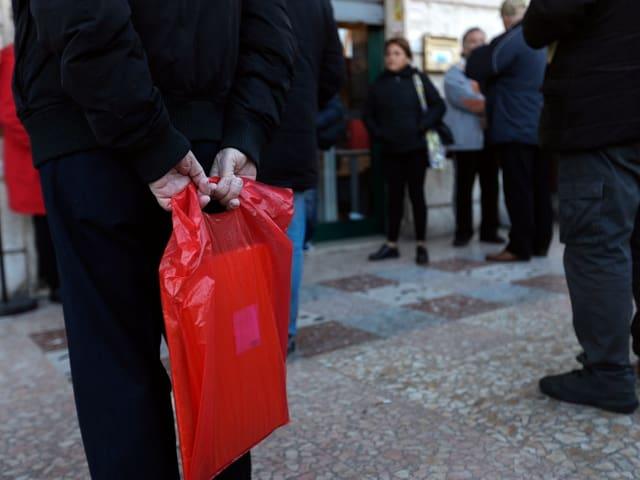 Bedürftige stehen Schlange vor einem Postbüro