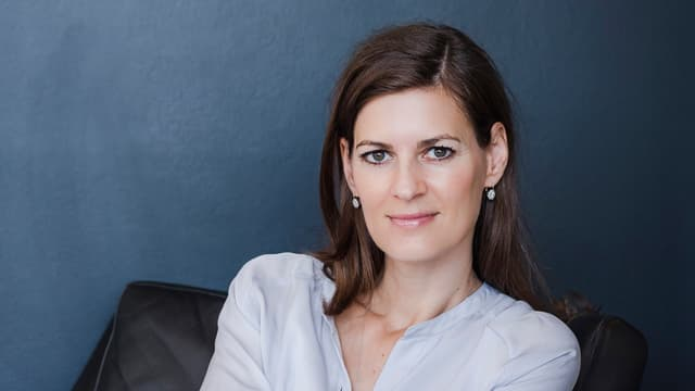 Sandra Konrad sitzt in einem Ledersessel.