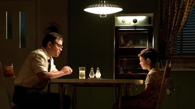 Vater und Sohn sitzen am Küchentisch.