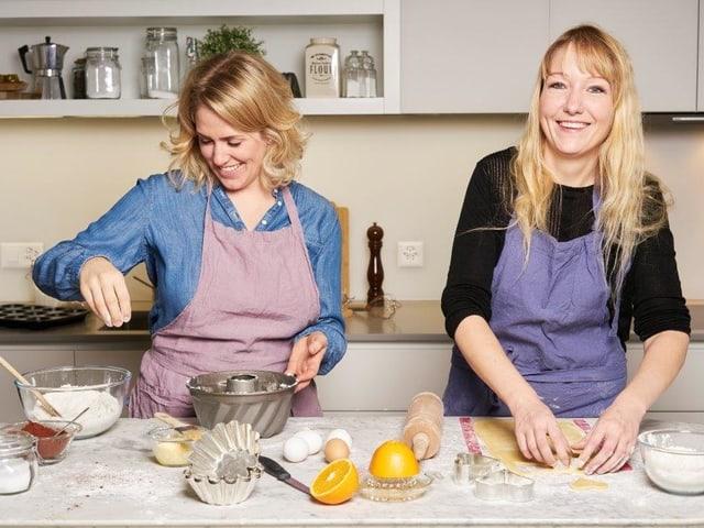 Katharina Rippstein und Claudia Boutellier stehen lachend in der Küche und backen.