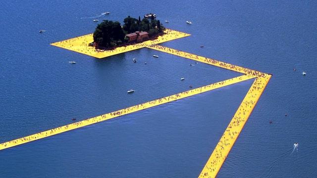Ein gelber Steg in Pfeilform auf einem See.