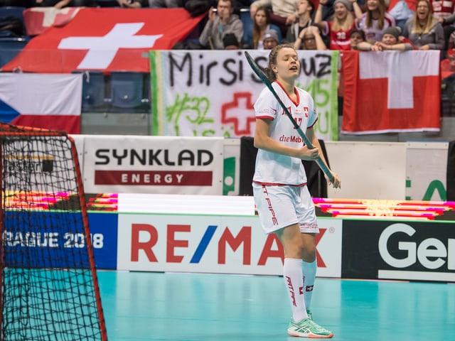 Unihockeyspielerin Isabelle Gerig steht neben dem Tor, im Hintergrund Schweizer Fans.