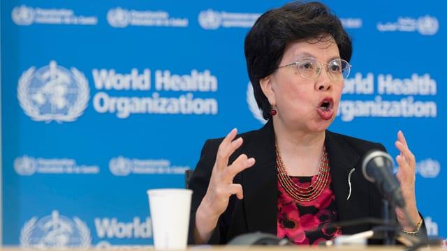 Die WHO-Präsidentin spricht vor einer blauen Wand, auf der das Logo der WHO mehrfachzu sehen ist.