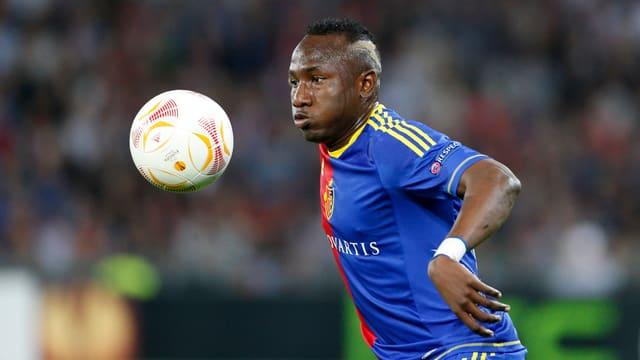 Zoua im Trikot des FC Basel nimmt einen Ball mit der Brust an.