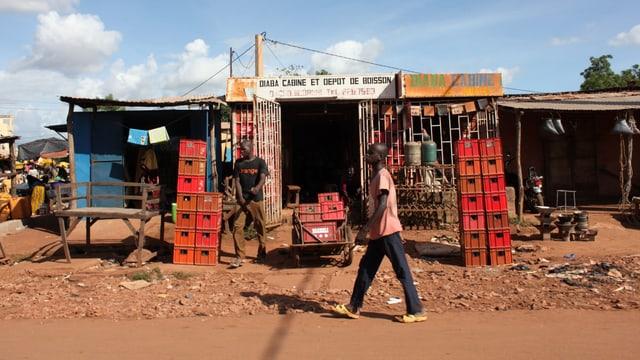 Ein Mann stappelt Getränkeharasse vor einem kleinen Laden. Ein Fussgänger geht daran vorbei.