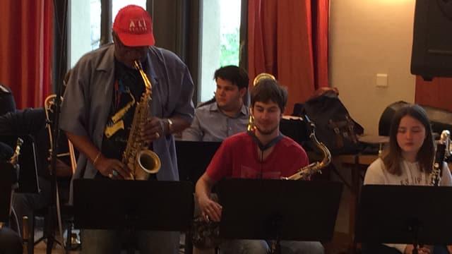 Ein Mann mit Käppchen spielt stehend Posaune, daneben sitzen einige Orchestermitglieder