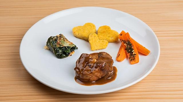 Hauptgerichtteller mit Fleisch, Polenta und Gemüse.