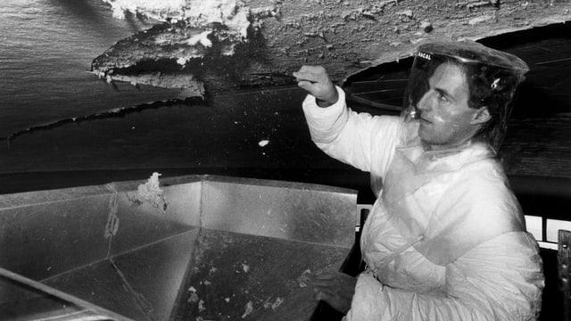 Ein Arbeiter befreit eine Decke von Asbest