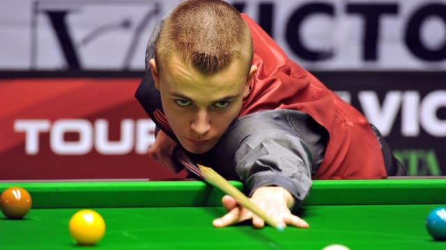 Alex Ursenbacher am Snookertisch, er zielt mit einem Queue auf eine Kugel.