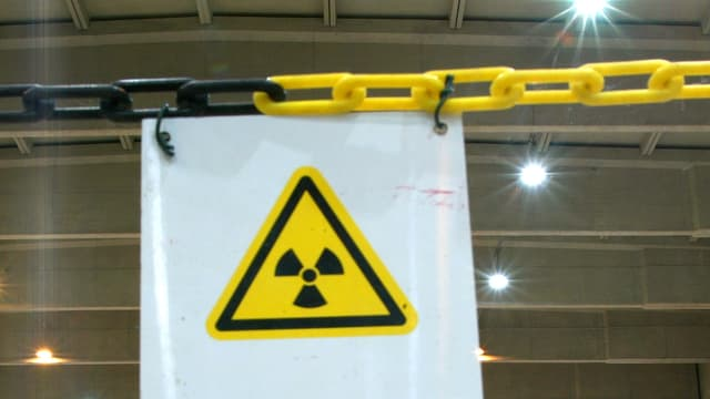 Weisses Warntransparent mit dem Symbol für Radioaktivität in gelbem Dreieck an einer Kette hängend