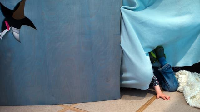 Kind versteckt sich hinter dem aus Tüchern gebauten Haus.