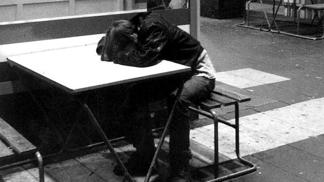 Schwarzweiss-Aufnahme eines Jugendlichen, der betrunken an einem Tisch im Freien schläft.